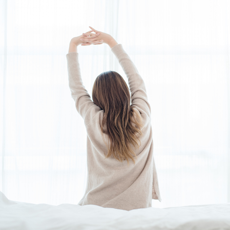 girl waking up and stretching after a peaceful night sleep on soft mattress