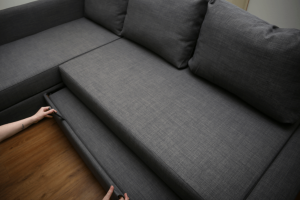 man pulling out a custom mattress from under a sofa